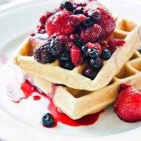 The Best Low Carb Waffles with a mixture of berries and sauce on top
