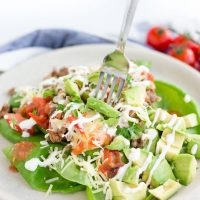 Image of Meal-Prep Low Carb Taco Salad on a plate with avocado, tomato, and sour cream drizzled on top.