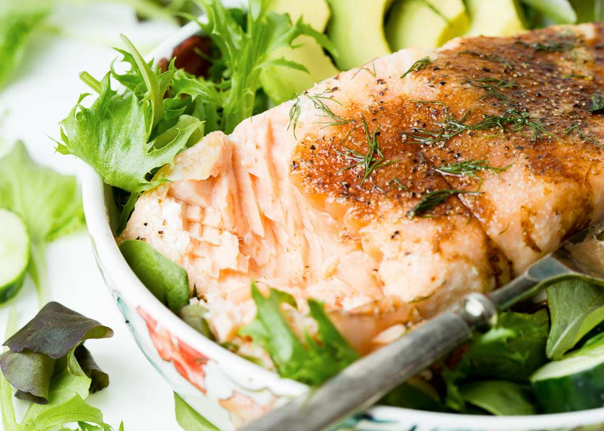salmon fillet on a salad with avocado