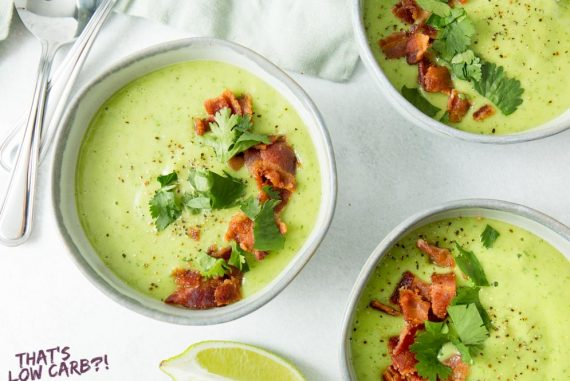 Overhead shot of Bacon Avocado Soup in three white bowls with quarter sliced lemon and two silver spoons beside them.