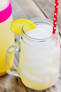 Keto Lemonade in a clear glass jar mug with lemon slice and straw next to pitcher.