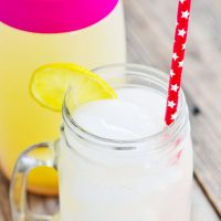 Image of Keto Lemonade in a clear glass jar mug with lemon slice and straw.