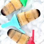 Image of three Keto Coffee Popsicle on ice with multi colored handles.