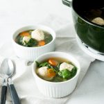 Image of Keto Low Carb Italian Wedding Soup in two white bowls with black handle spoons and a balck pot on either side laying on a white tea towel.