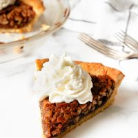 Image of Keto Pecan Pie with whip cream on top with the pie and forks blurred in the background.