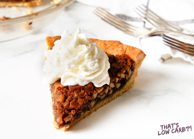 Image of Keto Pecan Pie with whip cream on top and three blurred forks in the background.