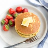 Image of Keto Pancakes with butter on top and strawberries beside.