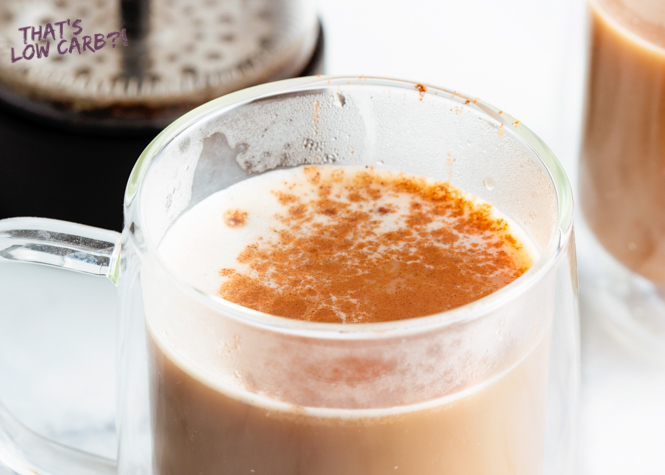 Image of Low Carb Keto Pumpkin Spice Latte in a clear glass mug with pumpkin spice sprinkled on top, with blurred second mug and french press in the background.