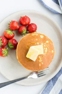 Overhead shot of Low Carb Pancakes with butter on top and strawberries beside.