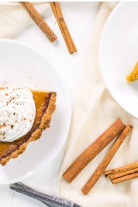 Overhead shot of Keto Low Carb Pumpkin Pie slices with whipped cream on top on white plates..