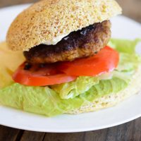 Low Carb Hamburger Buns on a burger with tomato and lettuce.