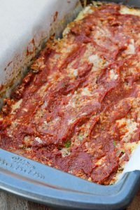 Image of Low Carb Meatloaf with red sauce on top in a bread pan lined with parchment paper.