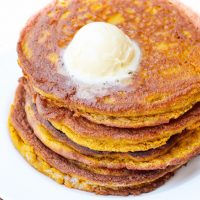 Image of low carb Pumpkin Pancakes stacked with butter on top on a white plate.