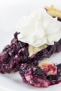 Image of keto low carb pie crust on blueberry pie slice with whipped cream.