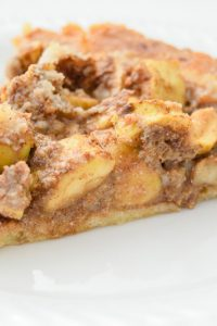 Image of a slice of keto mock apple pie on a white plate.