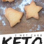 "PINTEREST IMAGE with words "" 2 net carb keto cut out cookies"" with image of keto cut out cookies on a wood cutting board and powder sugar sprinkled over top."