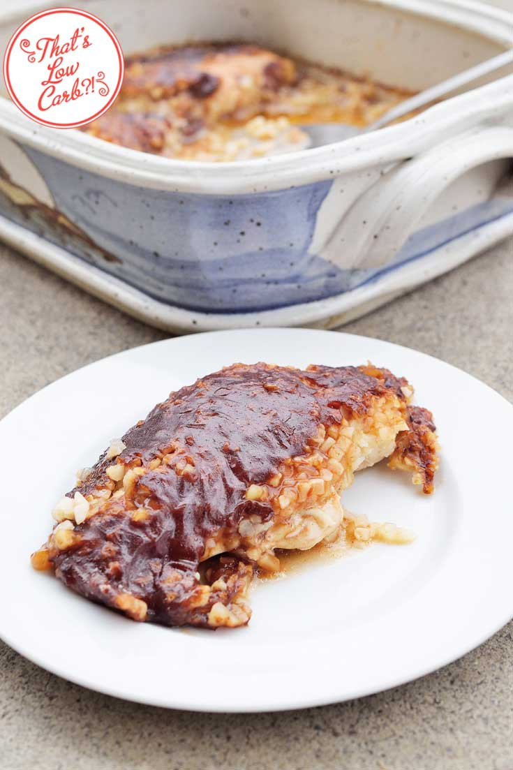 Low Carb Barbecue Ranch Chicken Casserole shown with one chicken breast, covered in barbecue sauce, displayed on a white plate while the remainder of the recipe sits in the casserole dish it was baked in, positioned behind the plate.