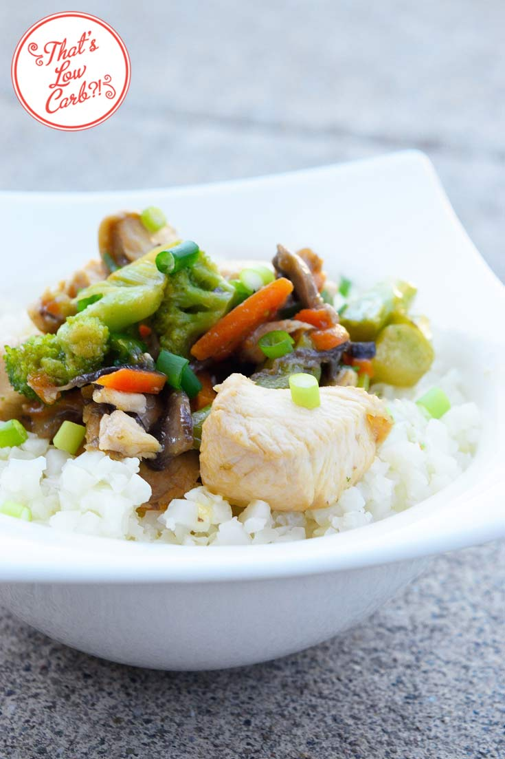 A bowl of Low Carb Teriyaki Chicken Stir Fry shown up close. The teriyaki chicken and vegetables rests on a bed of riced cauliflower in a white bowl.