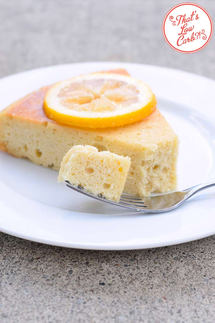 A slice of this low carb lemon cake sits on a white plate. It has a single lemon slice on top. A fork lays in front of the slice with a bit of the cake on it, ready to eat.