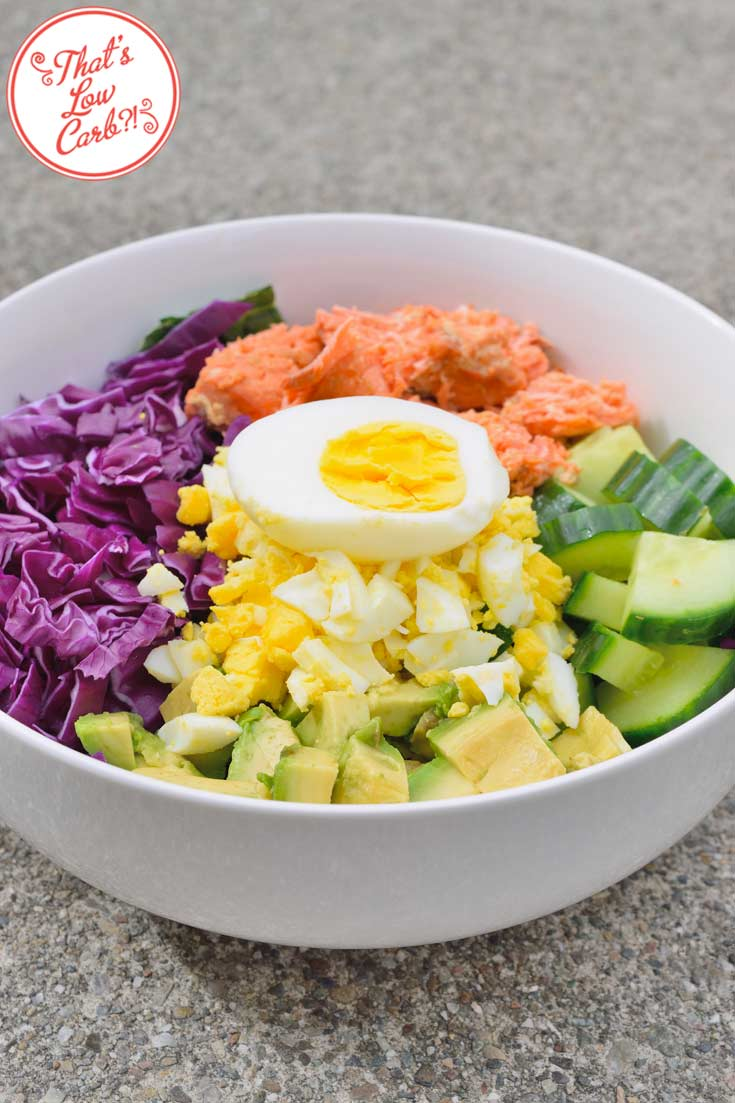 Low Carb Salmon Buddha Bowl pictured up close, showing the unmixed salad with each topping covering the kale. A half of a hard boiled egg sits on the chopped eggs in the middle of the bowl.