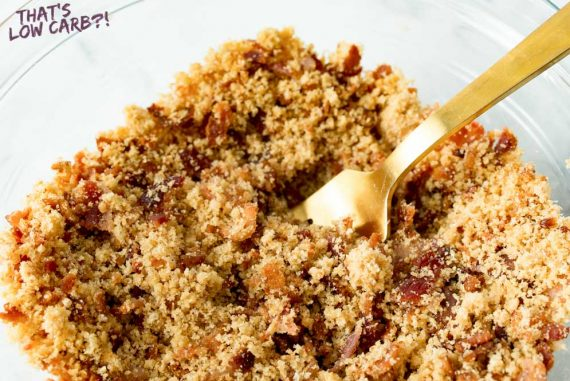 Image of keto low carb breadcrumbs in a glass bowl with a bronze fork sticking out.