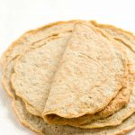 Image of low carb keto tortillas stacked with top one folded in half.