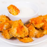 Low Carb Buffalo Chicken Nuggets on a white plate with one laying in a small bowl of ranch.