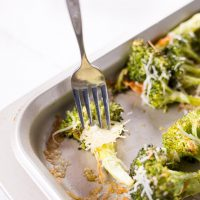 Oven Roasted Low Carb Broccoli on a baking sheet with cheese sprinkled over top and one being lifted by a fork.