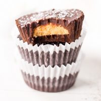 Low Carb Peanut Butter Chocolate Cups stacked with the top one missing a bite.