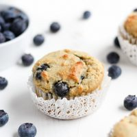 Low Carb Blueberry Muffins with blueberries spread around and a bowl of blueberries beside.