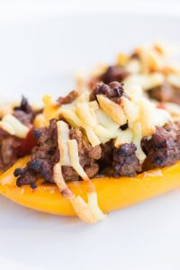 Low Carb Taco Stuffed Keto Peppers with cheese on top on a white plate.