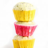 Low Carb Lemon Poppy Seed Muffins stacked three high with melted icing dripping down.