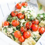 Image of Low Carb Artichoke Cheese Chicken Dinner in a casserole dish with spinach, goat cheese, and roasted tomatoes..