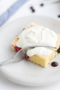 Image of Low Carb Raspberry Chocolate Sponge Cake square with whipped cream on top.