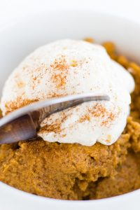 Image of Low Carb Keto Crustless Pumpkin Pie with whipped cream on top in a white bowl.