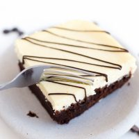 Image of Low Carb Cheesecake Brownie square with white frosting and chocolate drizzle being sliced by a fork.