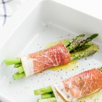 Image of low carb Asparagus Wrapped in Prosciutto laid out in a casserole pan with pepper and olive oil over top.
