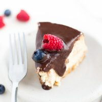 Image of Keto Cheesecake slice with chocolate sauce over top and raspberry and blueberry.