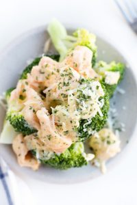 Overhead shot of Low Carb Smoked Salmon Cream Cheese Sauce over broccoli with Parmesan cheese sprinkled on top on a white plate.
