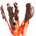 Image of Low Carb Chocolate Covered Bacon on wooden skewers standing straight up.