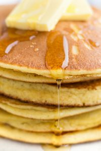Image of Low Carb Keto Maple pancake syrup drizzled over a stack of pancakes with butter on top.