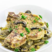 Image of Low Carb Pork Chops portion on a white plate with mushroom and green garnish on top.