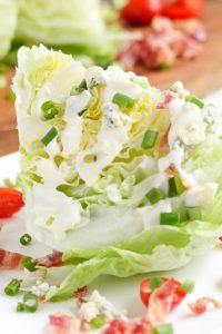 Image of Blue Cheese Low Carb Wedge Salad on a white plate with sliced tomato on the edges.