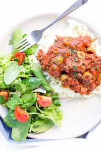 Overhead shot of low carb mexican picadillo on bed of rice on white plate with side salad.