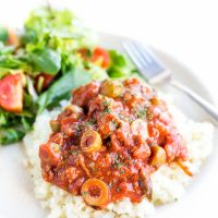 Image of low carb mexican picadillo on bed of rice on white plate with side salad.