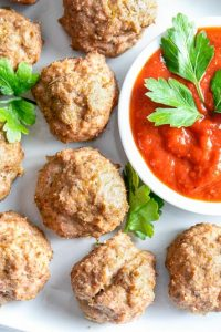 Image of Easy Keto Meatballs No Carb Meatballs on a white plate with a small bowl of red dipping sauce.