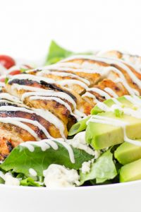 Image of Low Carb Buffalo Chicken Salad with tomatoes and avocado and white sauce drizzled on top.