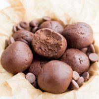 Image of Keto Peanut Butter Chocolate Bombs in a bowl with center one missing a bite with parchment paper with chocolate chips on top.