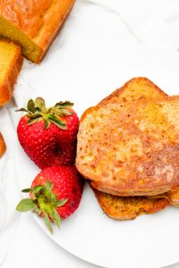 Image of Keto French Toast with strawberries on a white plate with slices laid out beside.