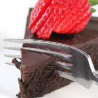 Image of Keto Flourless Chocolate Cake slice with strawberries on top with a fork slicing off a bite.